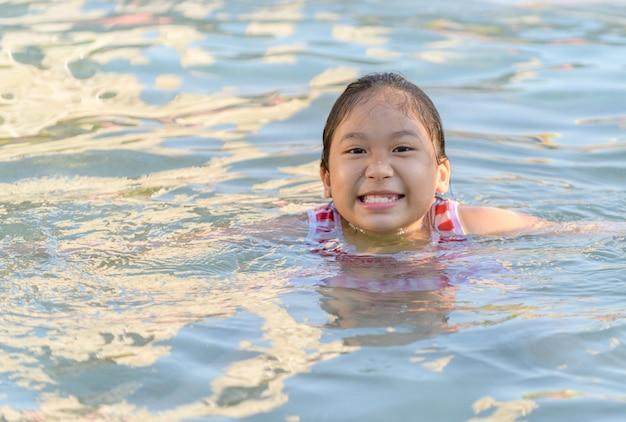 晴れた日にプールで笑顔のかわいい女の子