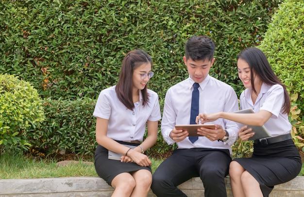 Азиатские студенты с помощью планшета, чтобы сделать домашнюю работу в университете,