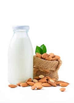 Бутылка молока и миндальных орехов с листом, изолированных на белом фоне,