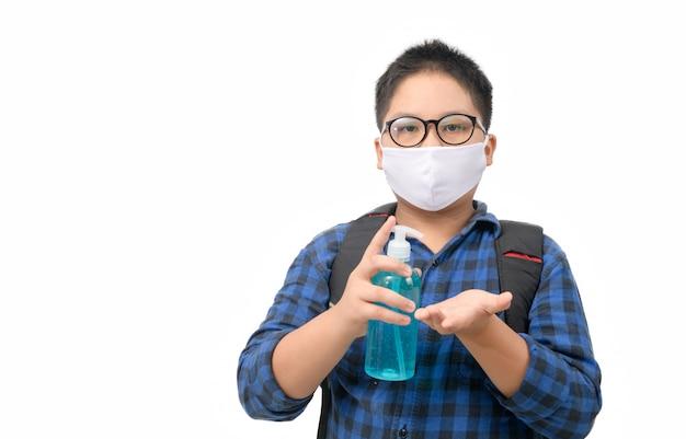 アジアの少年学生着用マスク白で隔離アルコールゲルボトルを保持