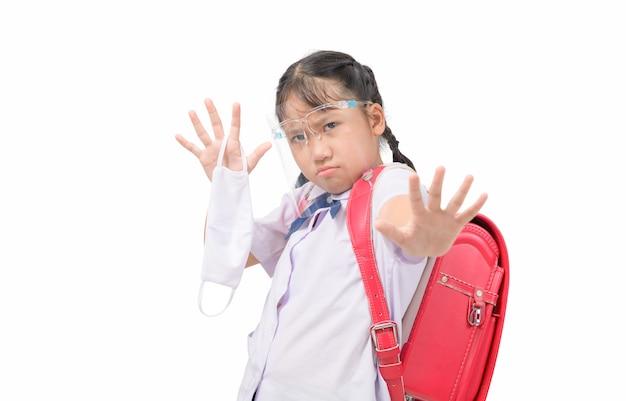 シールドの顔を身に着けているアジアの学生少女と感染性ウイルスに対する布のマスクを保持し、ストップジェスチャーを示す