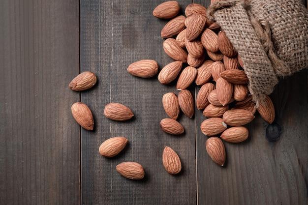 木のテーブルの袋に皮をむいたアーモンドナッツ。アーモンドは非常に人気のあるナッツと高タンパク質です。健康食品。