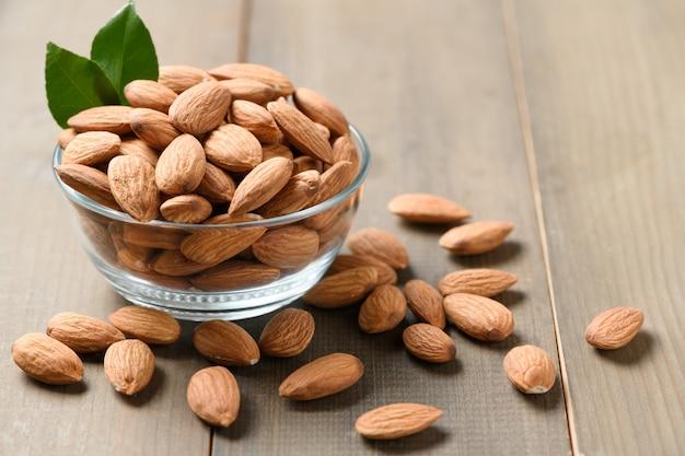 木製のテーブルのガラスのボウルに皮をむいたアーモンドナッツ。アーモンドは非常に人気のあるナッツと高タンパク質です。健康食品。
