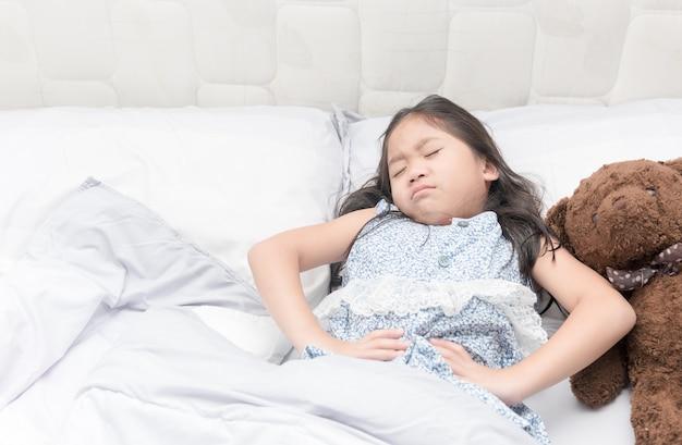 У маленькой девочки в постели боль в животе