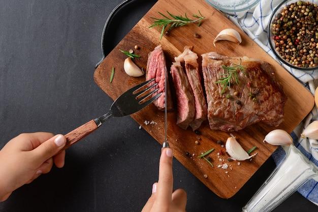 トップビューで牛肉ステーキを切る小さな手