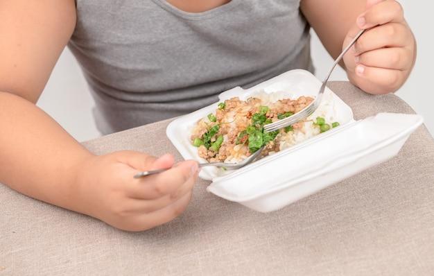 泡のボックスで揚げた米を食べる肥満脂肪男の子