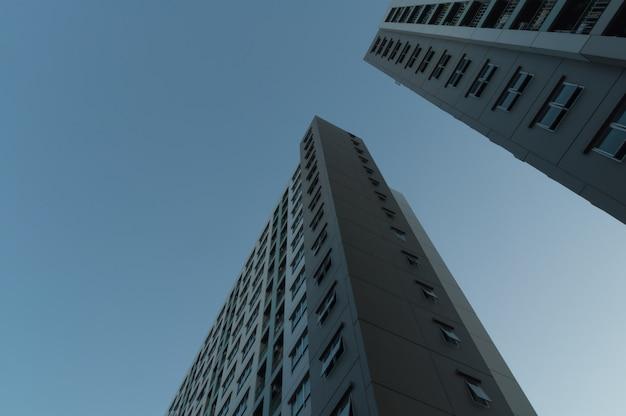 レンズフレアフィルター効果と夕暮れ時の宿泊施設の近代的な高層ビルの底面図
