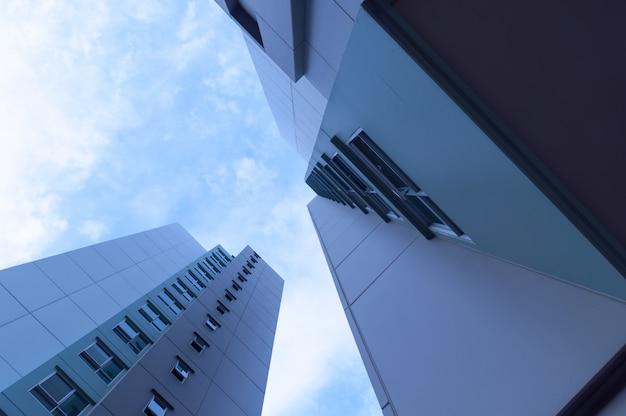 レンズフレアフィルター効果と夕暮れ時の宿泊施設の近代的な高層ビルの底面