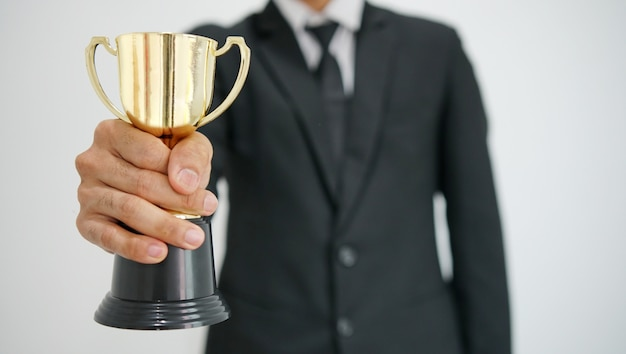 Бизнесмен, держа трофей. концепция успеха в бизнесе.
