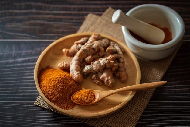 ウコン粉末と木製の皿にウコン根