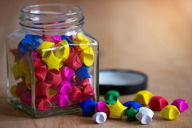 朝の日差しで木製のテーブルの上の正方形のガラス瓶の中の多色紙の星。