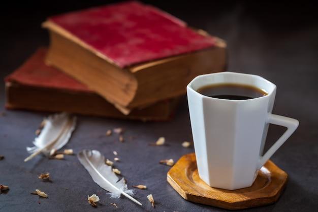 白いカップと羽とドライフラワーの花びらを持つ古い本でブラックコーヒー。