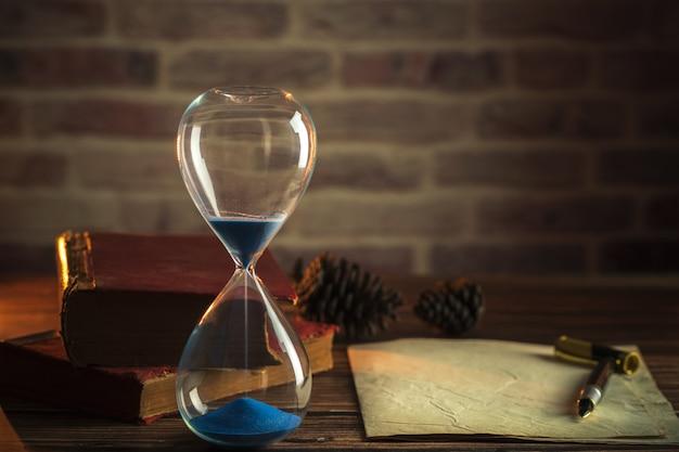 砂時計と古い本とランタンの照明で木製のテーブルの上にペン。