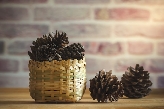 Конус сосны в бамбуковой корзине на предпосылке деревянного стола и кирпичной стены с солнечным светом утра.