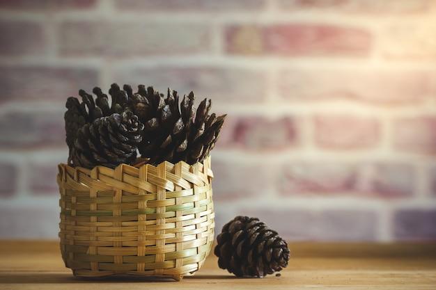 木製のテーブルと朝の日差しでレンガ壁の背景に竹かごで松ぼっくり。