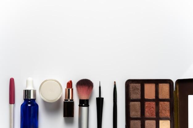 化粧や白い背景の上の女性の美しさのための多くの化粧品。