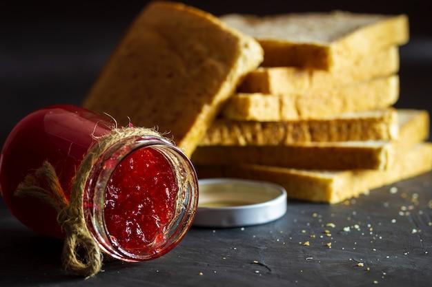 Бутылка клубничного варенья и хлеб из цельной пшеницы сложены