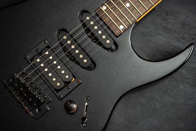 黒いセメントの床に黒いエレキギター。上面図とコピースペース。ロックミュージックのコンセプトです。