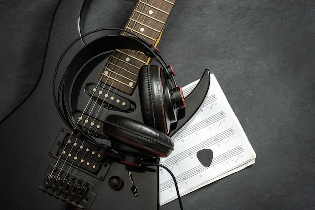 床に黒のエレキギターとヘッドフォン。