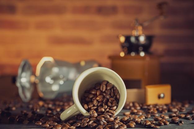 木製のテーブルに白いカップとコーヒーグラインダーでコーヒー豆。朝の朝食またはコーヒータイム。
