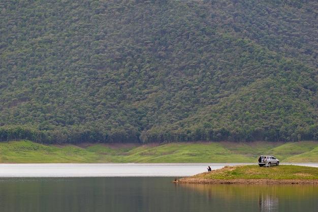 山に囲まれたダムの島に座って釣りをする男性。