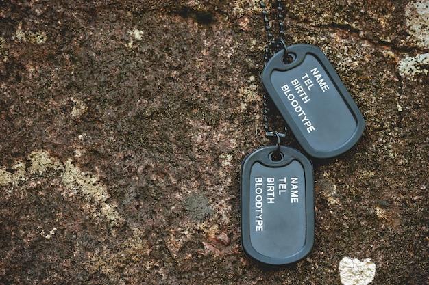 Военный тег повешен на скале на фоне скалы в лесу. концепция жертвоприношения и перемирия солдата.