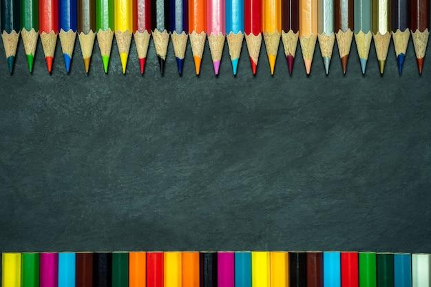 黒板背景に色鉛筆。トップビューとコピースペース。美術教育のコンセプトです。