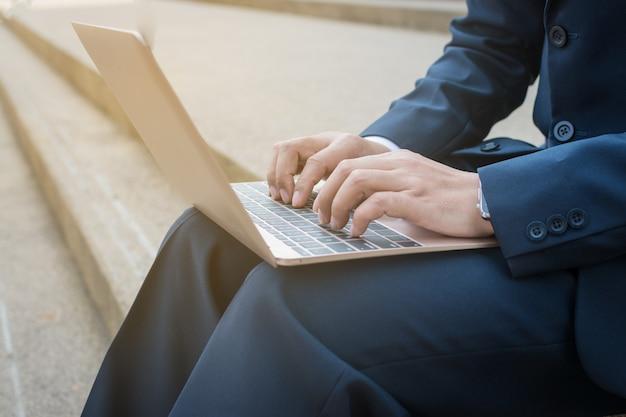 ビジネスマンが屋外でコンピューターを使用する