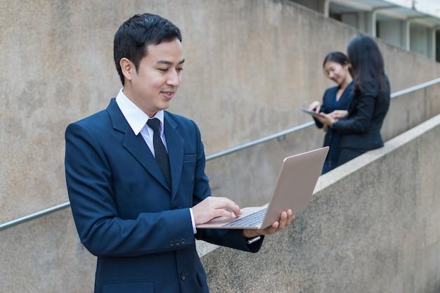 ビジネスマンは屋外のラップトップを使用してください