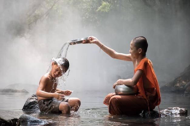 Монах и мальчик играют в воду