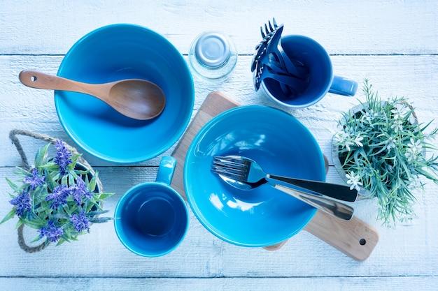 白い木のテーブルの背景に植木鉢と台所用品