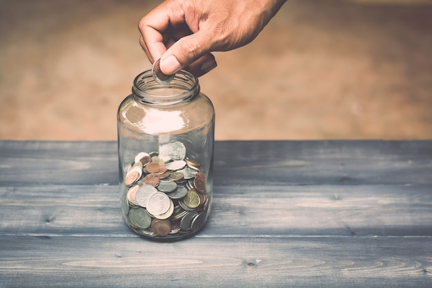手は貯金のためにガラス瓶にお金を落とす