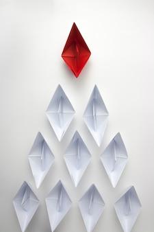 白い紙をリードする赤い紙の船