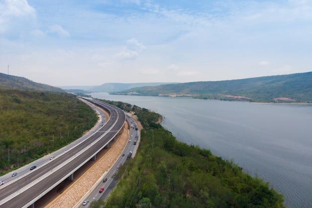 大きな自然の川の近くの建設中の高速道路通行料の下のドローンショット空撮風景