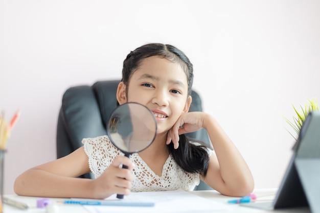 Маленькая азиатская девушка используя увеличитель делая домашнюю работу и улыбку с счастьем для концепции образования выберите фокус малую глубину поля