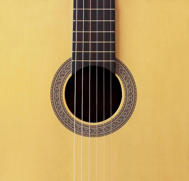 抽象的な背景に木製のスペインの古典的なギターの穴にナイロンひも