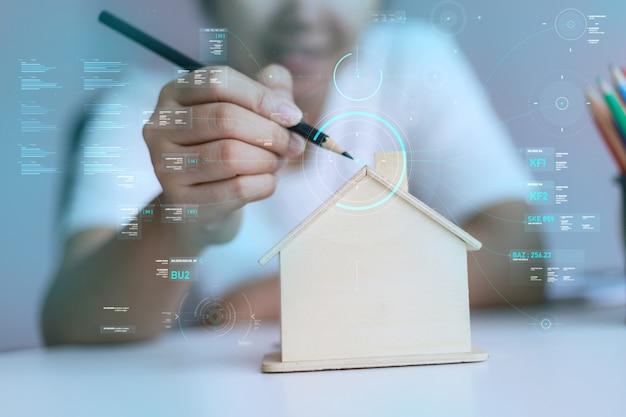木造住宅貯金箱とサイバー技術で描くために鉛筆を使用して幸せなアジアの女性