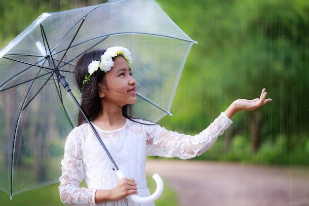 Маленькая азиатская девушка держа ясный зонтик и усмехаясь с счастьем