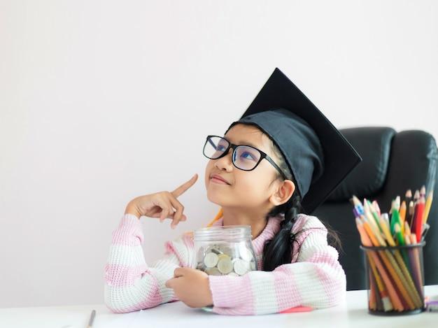 Маленькая азиатская девушка в шляпе выпускник обнимает прозрачную стеклянную банку