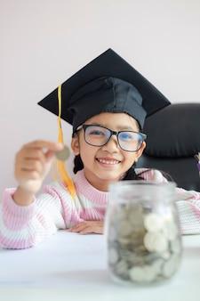 Маленькая азиатская девушка в выпускной шляпе положить монету в прозрачную стеклянную банку