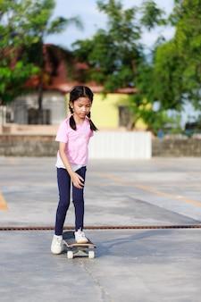 Азиатская маленькая девочка играет скейтборд
