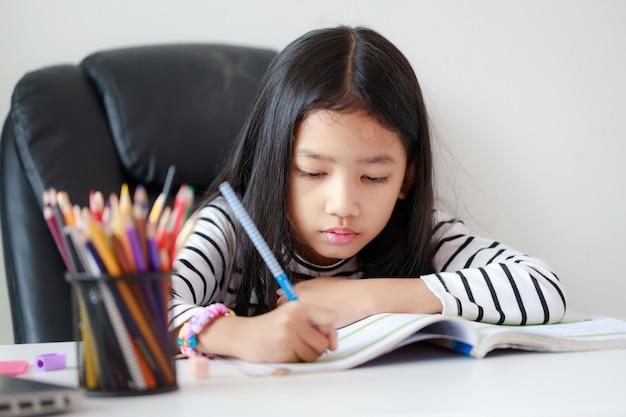 Маленькая азиатская девушка делает домашнее задание