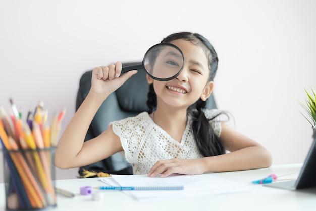 Маленькая азиатская девушка используя увеличитель делая домашнюю работу и улыбку