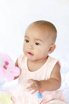 座っているかわいいアジアの赤ちゃんと幸せと遊ぶ浅い被写し界深度を選択します。