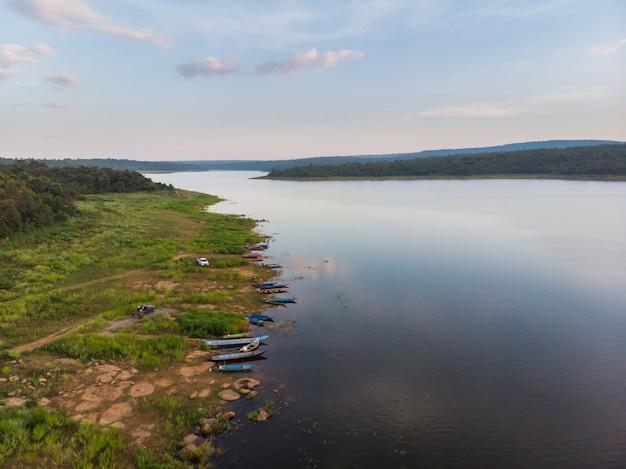 Дрон выстрелил с высоты птичьего полета живописный пейзаж рыбацкой лодке в большой реке со свежим зеленым деревом и пляжем