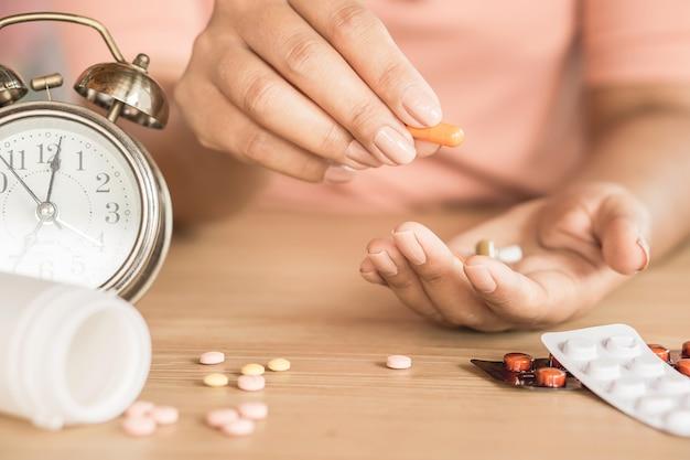 Женщина рука принимая таблетки с часами на столе