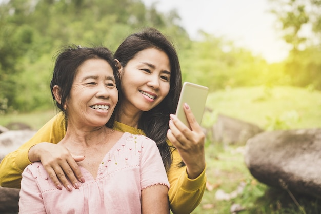 幸せなアジアのお母さんと娘が一緒にスマートフォンのセルフの写真を使用