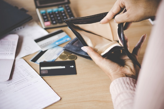 貧しいアジアの女性の手が開いて空の財布お金を探して