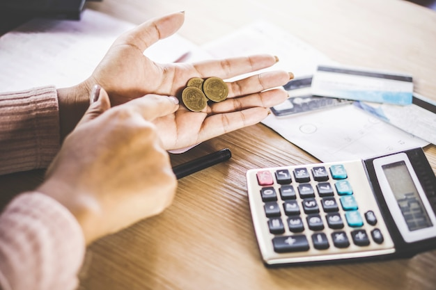 クレジットカードを支払った後に貧しい女性の手が硬貨を持っている