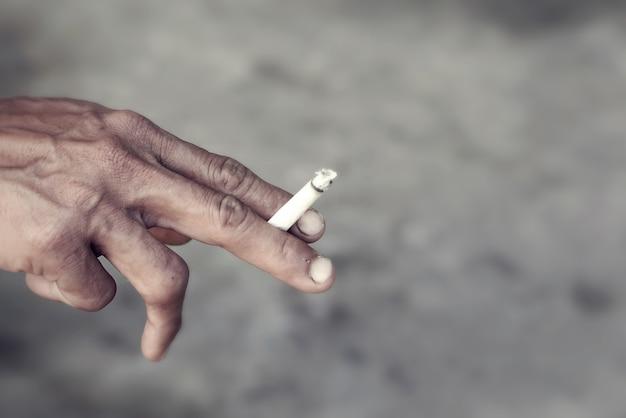 燃えているタバコを握っている男の手